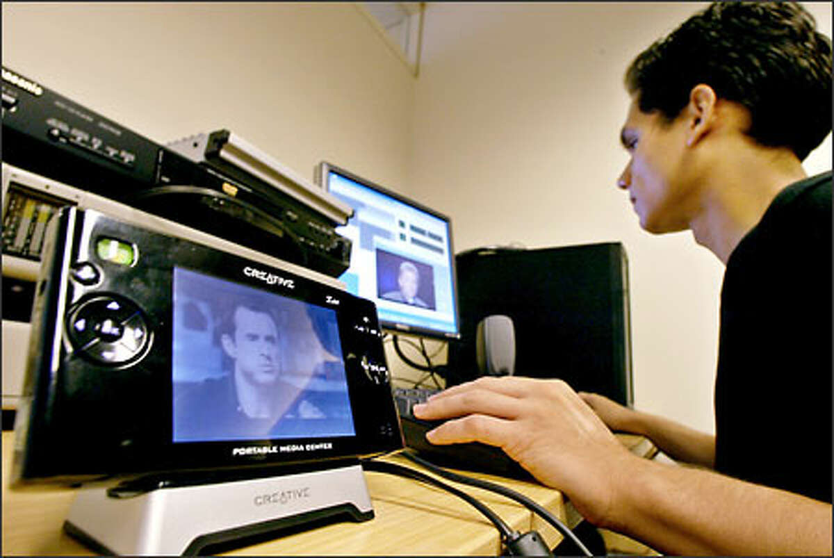 """Bobby Kanaeaupuni of CinemaNow in Santa Monica, Calif., encodes a film in preparation for the launch of Microsoft's """"portable media center,"""" playing in the foreground. Users will be able to download movies and watch them."""