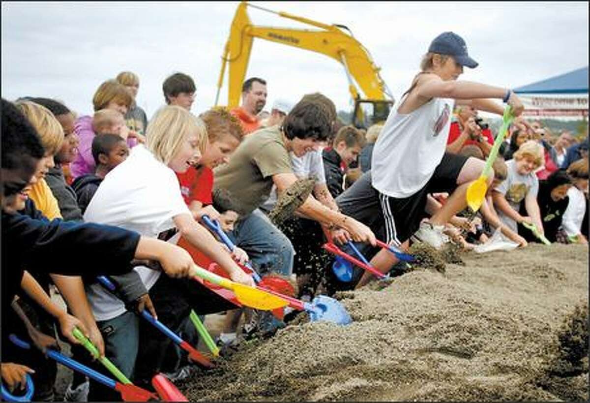 Youngsters armed with plastic shovels break ground Tuesday at the site of The Landing, which is near Fry's Electronics in Renton. Prizes were buried in the sand.