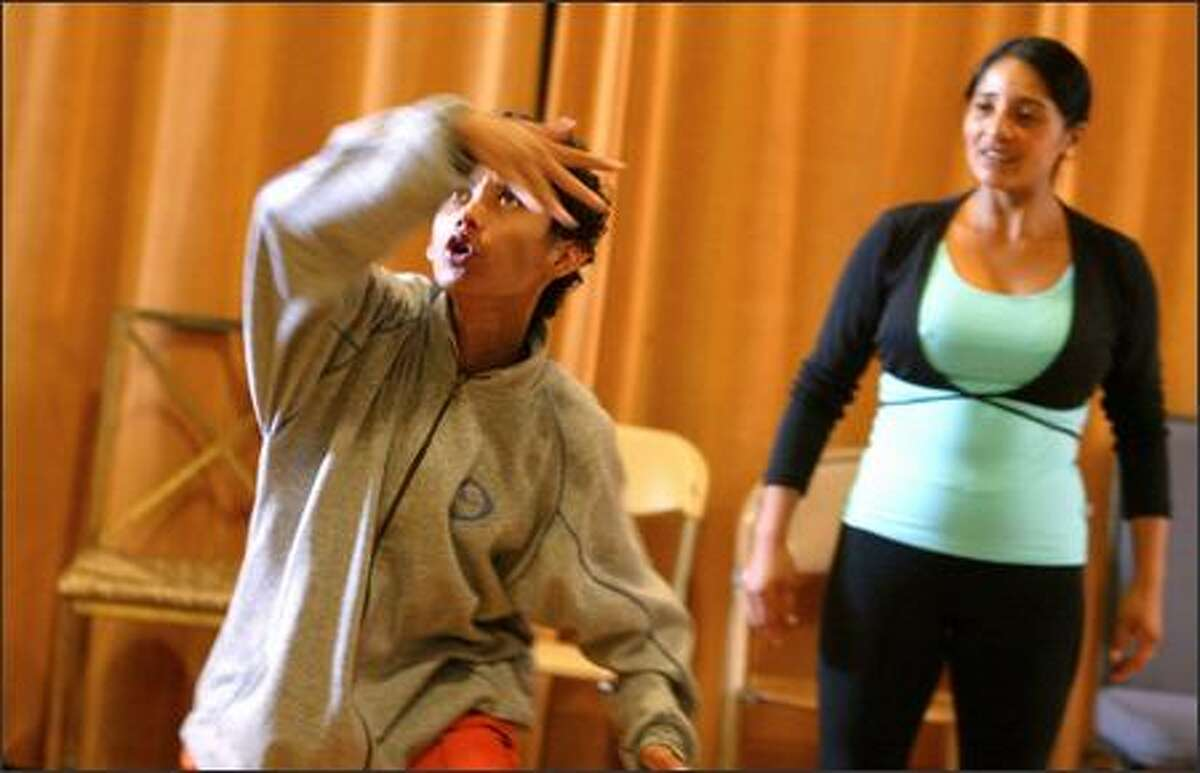 Oscar Valladaro, 19, of Nicaragua performs a warm-up exercise at Freehold Theater's performance space as classmate Tatiana Amoba of Ecuador prepares to mimic him.