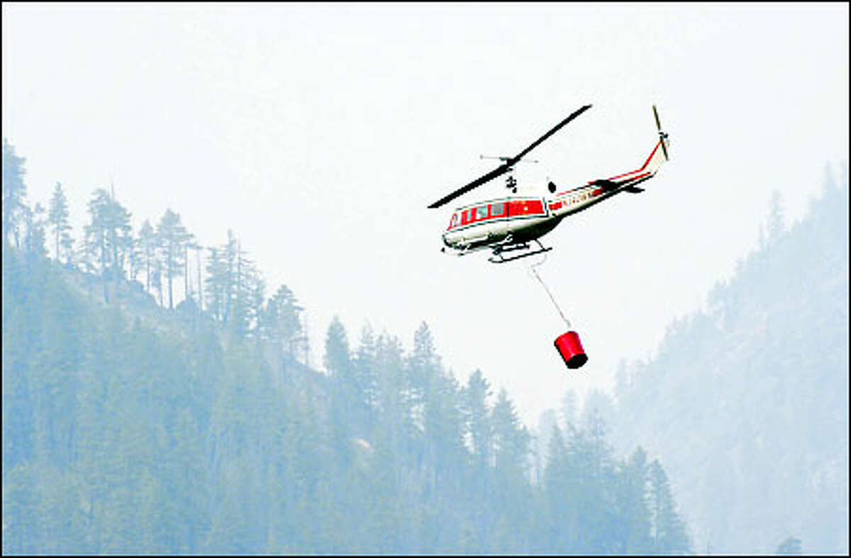 A helicopter takes off near the Leavenworth National Fish Hatchery yesterday to drop water on a fire at nearby Icicle Ridge. As many as 100 area homes were threatened.
