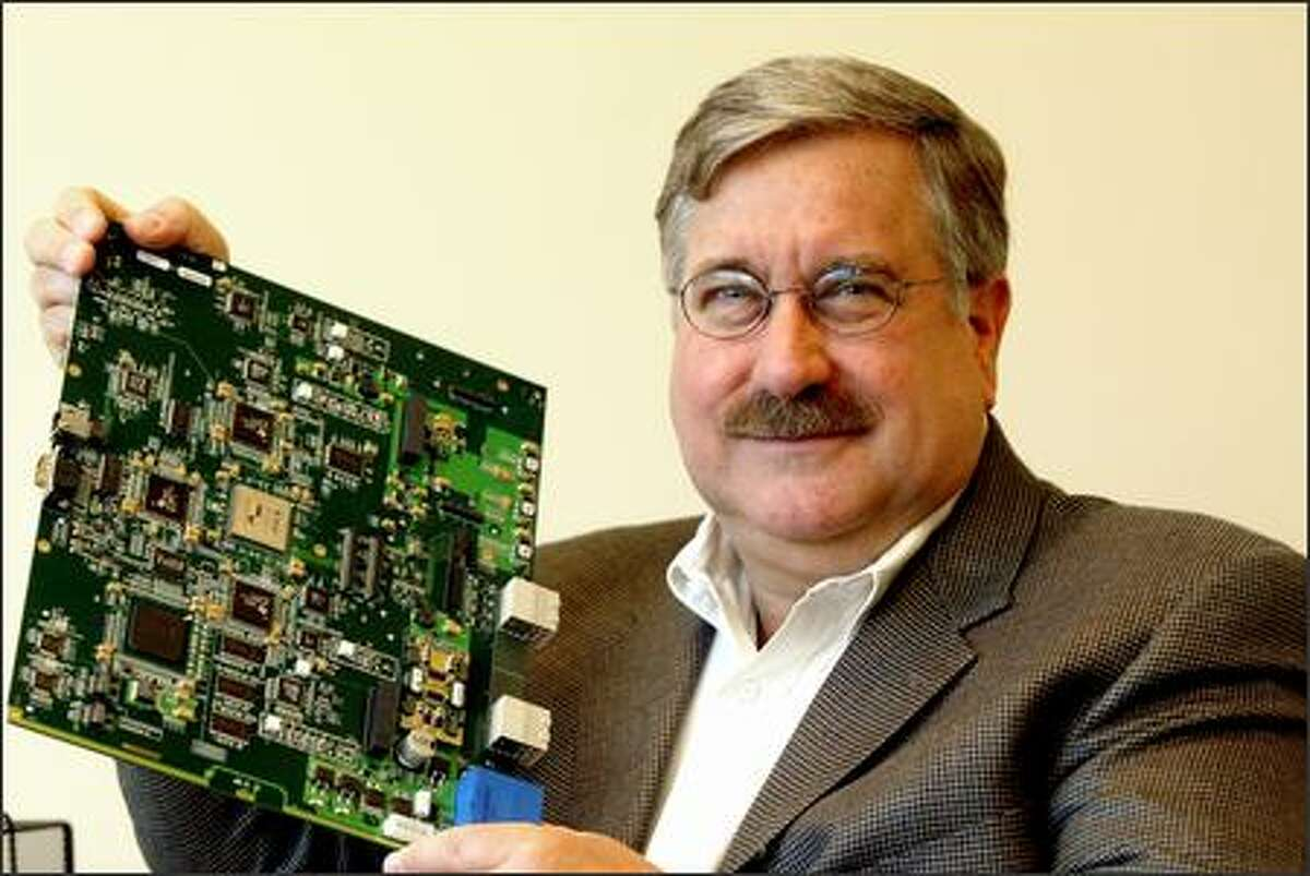 Adaptix CEO Vern Fotheringham displays a base station board that can be used in supplying high-speed Internet access to large areas.