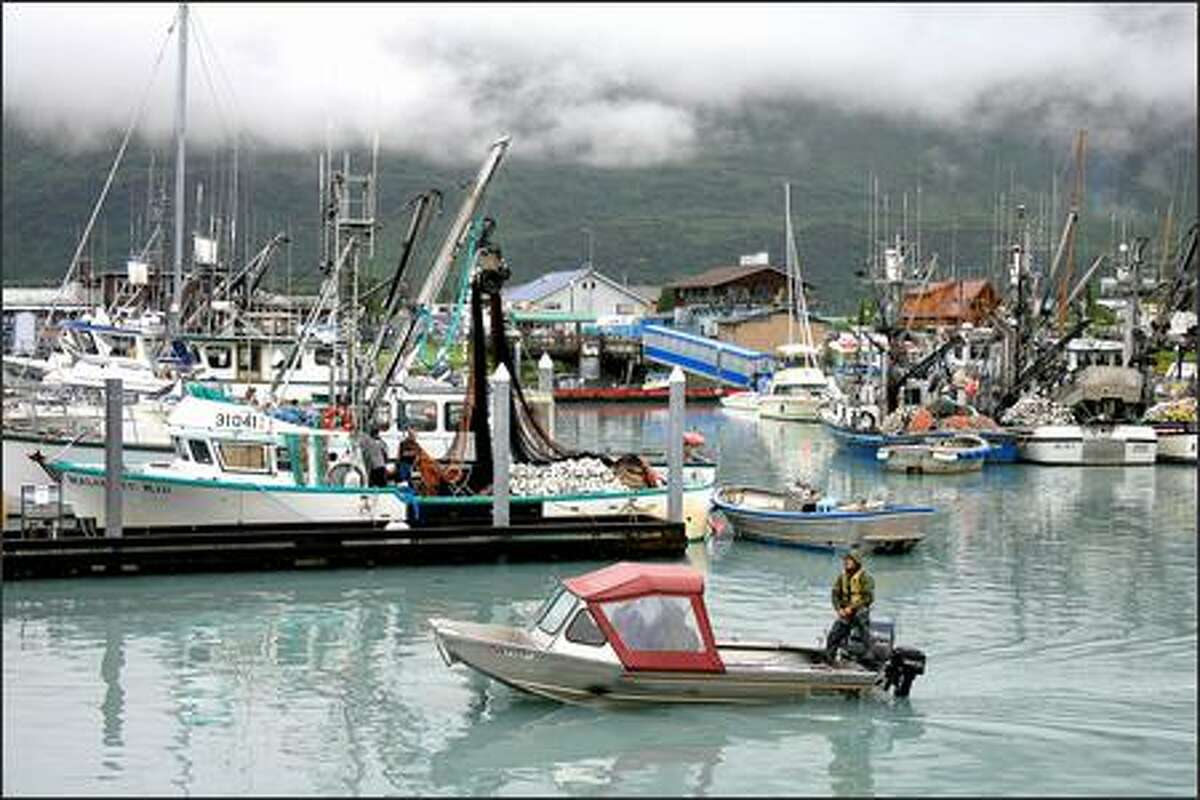 A boat motors out of the harbor in Valdez, Alaska, past docks with commercial fishing boats mixed in with personal boats.