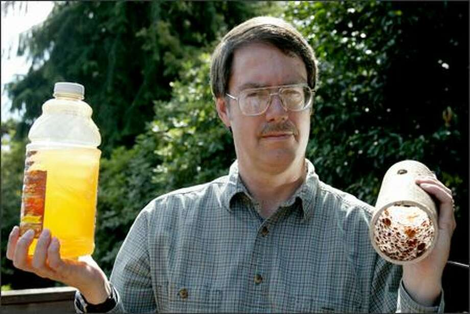 Mark Cooper holds a bottle of orange-colored water he took from the tap at Wedgwood Elementary, where his children go to school. Photo: Scott Eklund, Seattle Post-Intelligencer / Seattle Post-Intelligencer