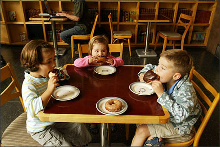 After getting their haircuts the other day, Clara, 4, Esther, 2, and Hugo Schachermalyr, 6, from left, dive into some doughnuts at Top Pot Doughnuts. Photo: Phil H. Webber, Seattle Post-Intelligencer / Seattle Post-Intelligencer