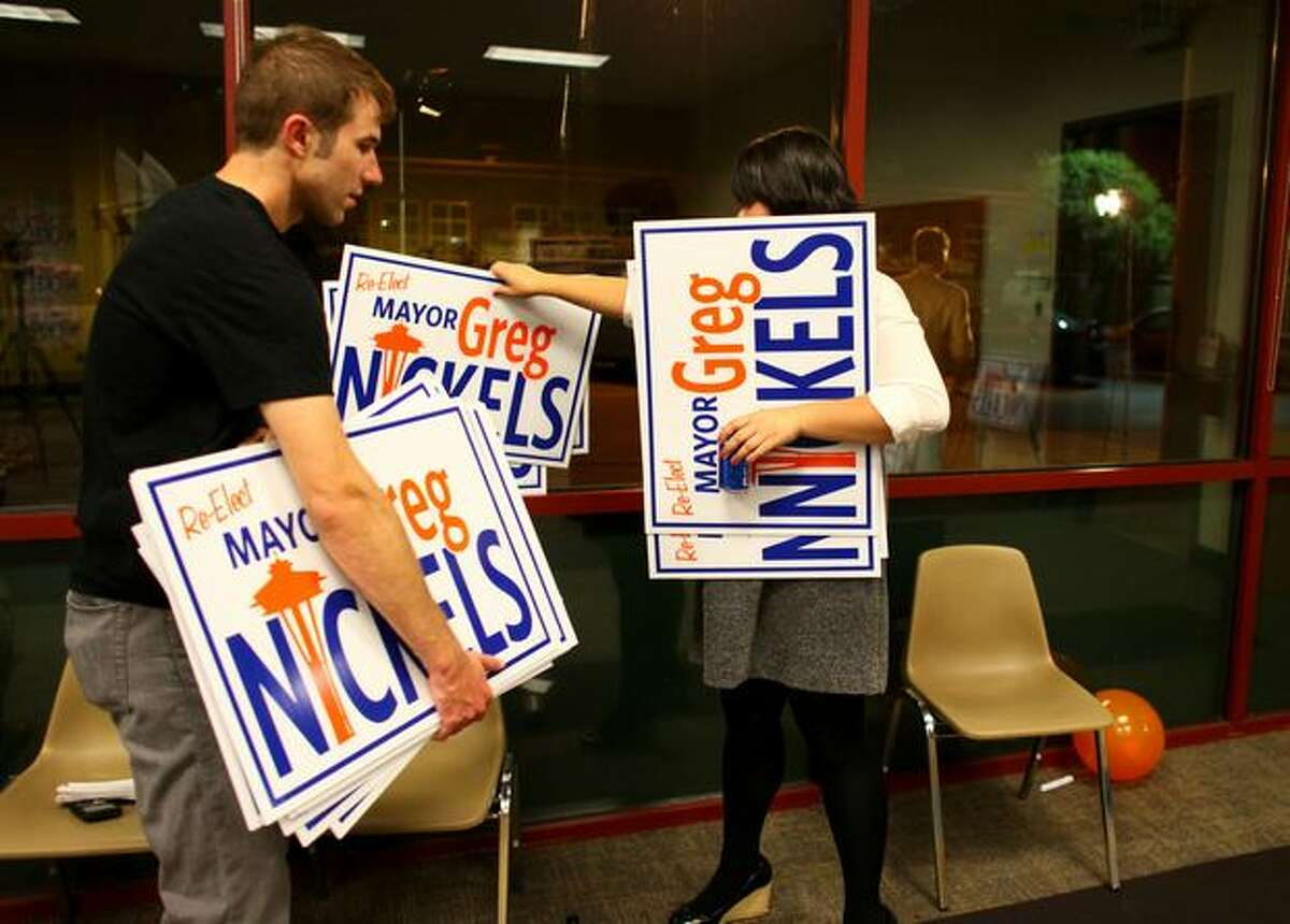 Ryan Petersen, left, and Priscilla Min gather campaign signs after a party for the Mayor Greg Nickels campaign in Sodo. The mayor spoke to his supporters after early returns showed him in third place.