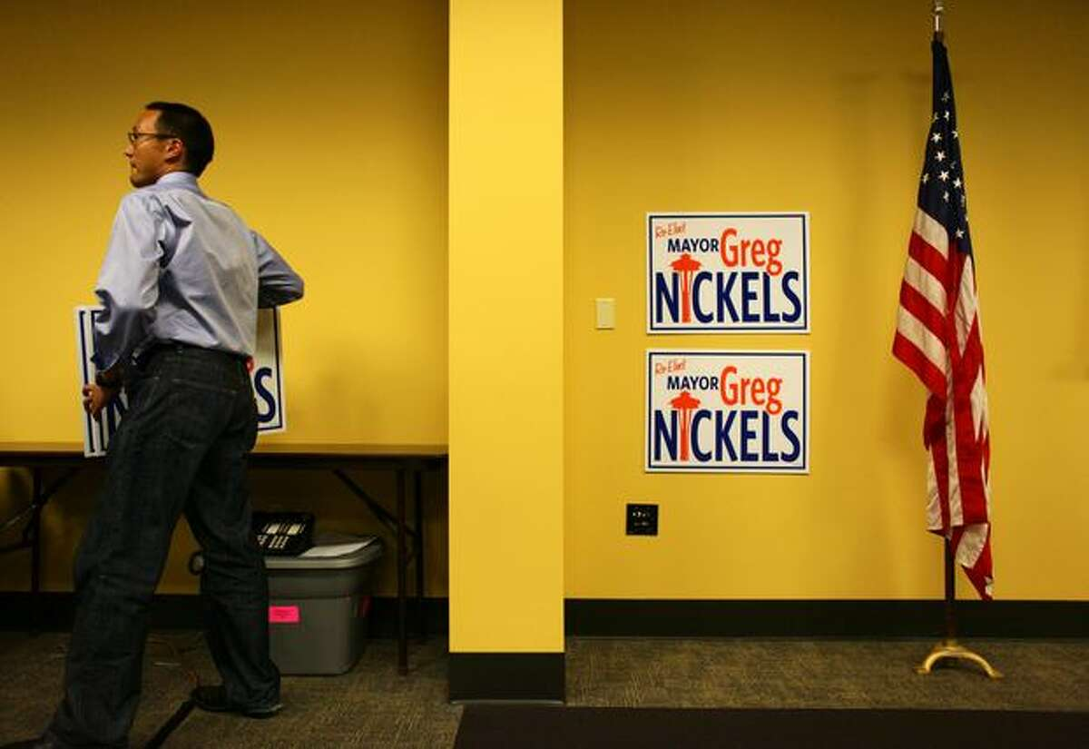 Julien Loh helps gather campaign signs after a party for Nickels.