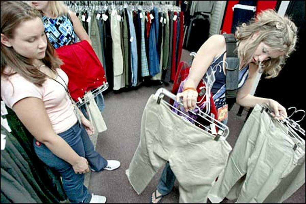 At the recently opened Plato's Closet consignment store in Lynnwood, employees Janelle Label, right, and Kari Kosnik look over a selection of famous-maker pants for a customer.