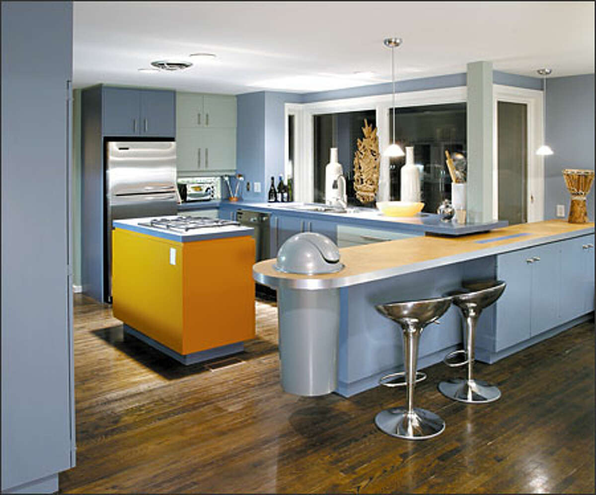 A watery blue and green color scheme, with islands of bold orange, punches up this once-bland kitchen.