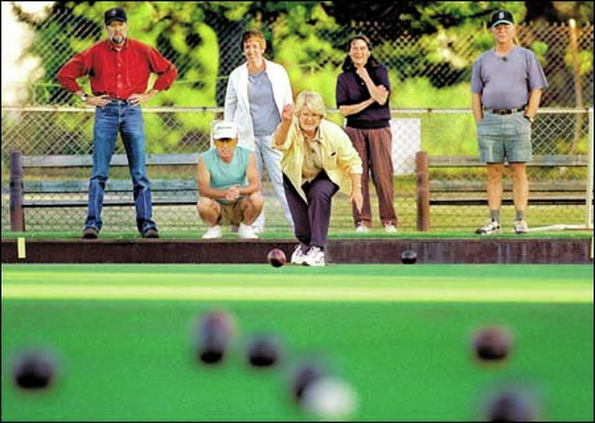 Jo Ann Erickson tries lawn bowling for the first time. With her are, left to right, Colon Williams, Its Nishikawa, Shelley Williams, Marge Caddey and John Erickson.