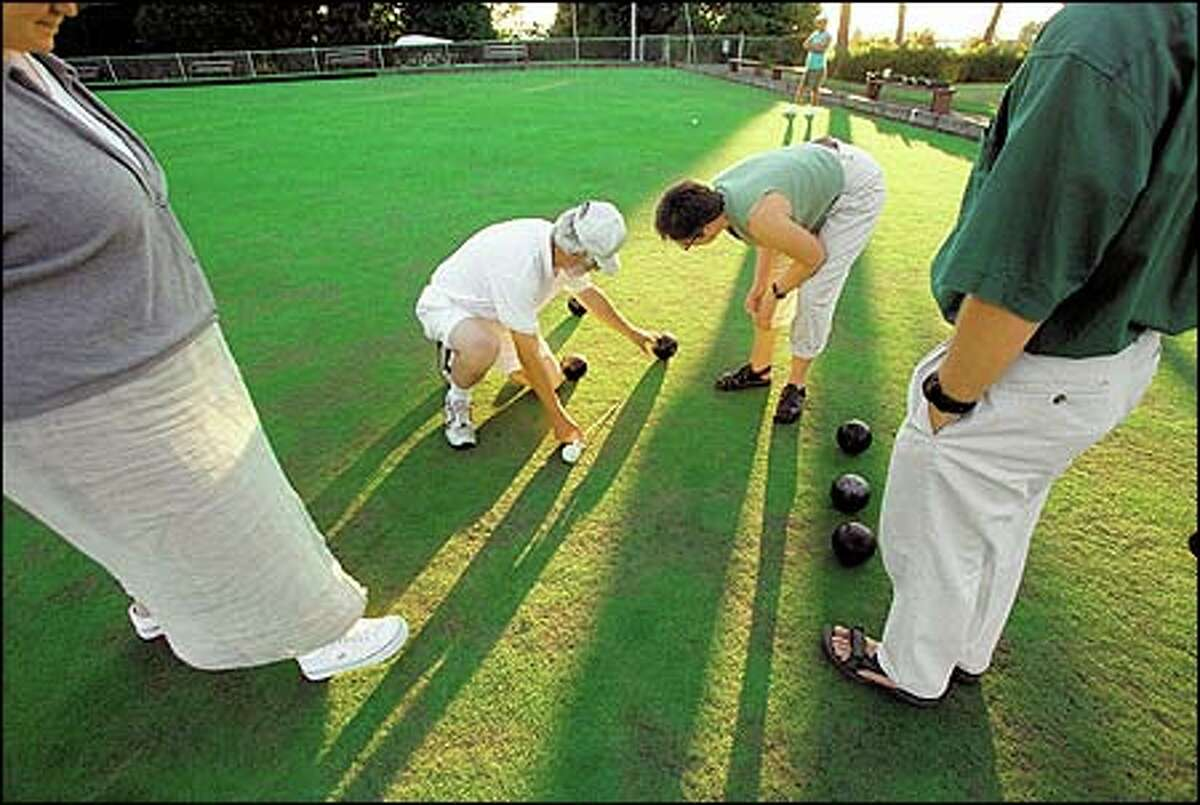 Accurate measurement, here handled by Chuck Caddey, center, in Seattle's Jefferson Park, is essential in the anti-extreme sport of lawn bowling, a game fit for any age seeking exercise without exercising.