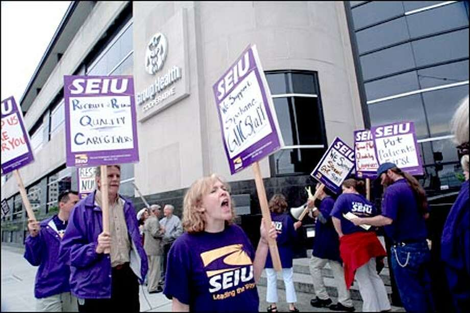 Rebecca Johnson, organizer for SEIU Local 1199, center, was one of about 30 health care workers who picketed outside Group Health Cooperative's main administrative offices in downtown Seattle yesterday to support striking Group Health employees in Eastern Washington and Northern Idaho. Demanding higher pay, about 100 nurses and therapists at Group Health clinics in Spokane and Coeur d'Alene, Idaho, staged a one-day strike yesterday. Photo: Phil H. Webber, Seattle Post-Intelligencer / Seattle Post-Intelligencer