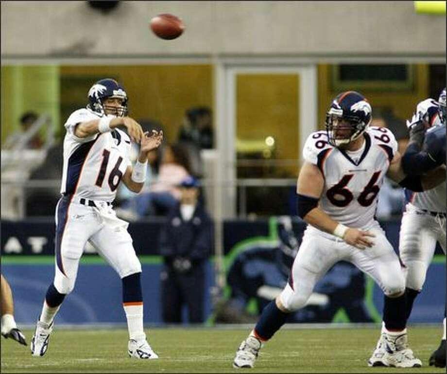Denver Broncos' quarterback Jake Plummer gets a pass off in the second quarter as Broncos' center Tom Nalen (66) helps block. (AP Photo/Ted S. Warren) Photo: Associated Press / Associated Press