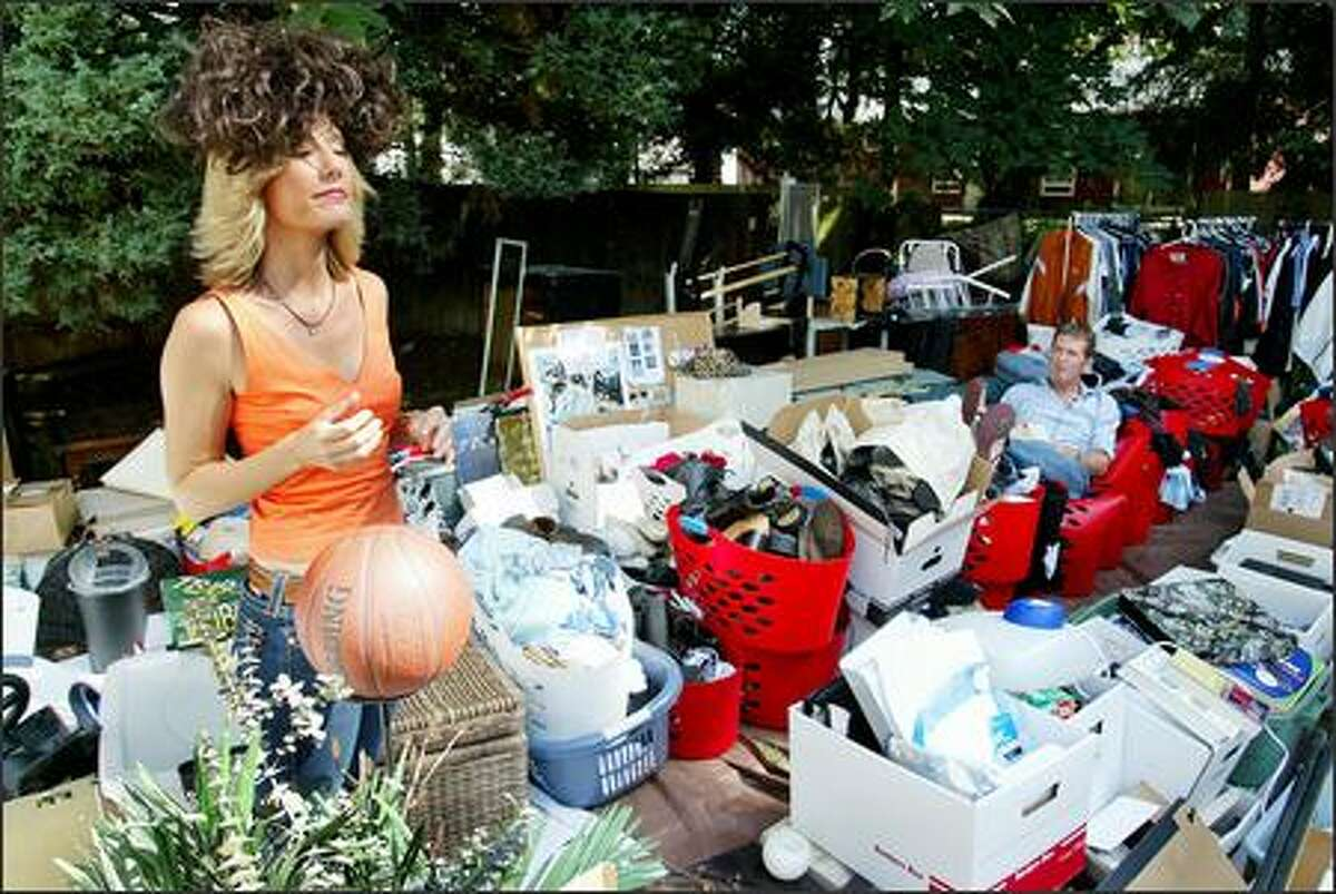 """""""Clean Sweep"""" host Tava Smiley enjoys a wig she found among the belongings of John and Stacey Olsen during taping of a segment for the TLC show. At right is Peter Walsh, whose role on the show is to reorganize selected rooms of the home."""