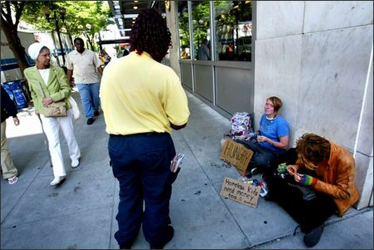 Dalana Slaughter, safety supervisor of the ambassadors who patrol Seattle for the Give Smart campaign, speaks to two teenagers sitting on a downtown sidewalk.