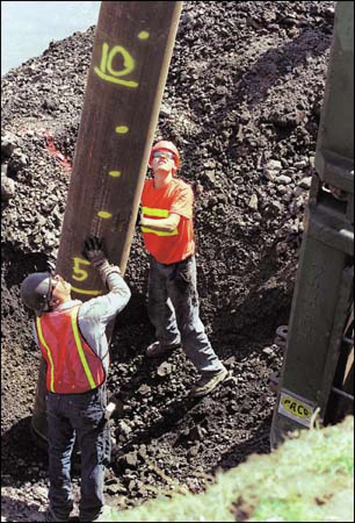 Bill Hobson, a journymen pile driver, and Jeremy Nielsen, an apprentice pile driver, place a pile at Pier D on the Tacoma waterfront.