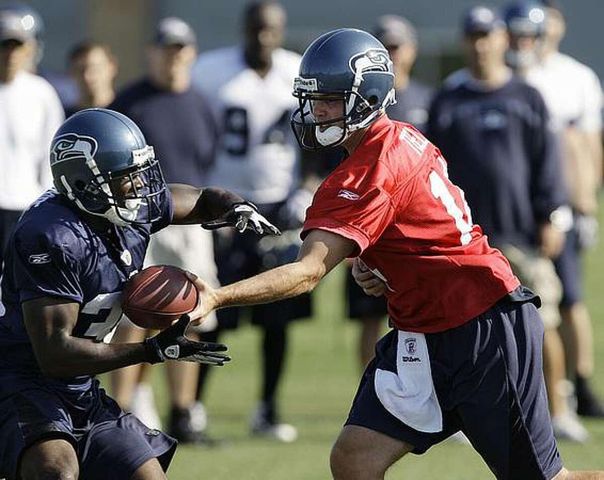 Seattle Seahawks backup quarterback Mike Teel, right, hands off to Devin Moore during NFL football training camp Aug. 20 in Renton. (AP Photo/Elaine Thompson)