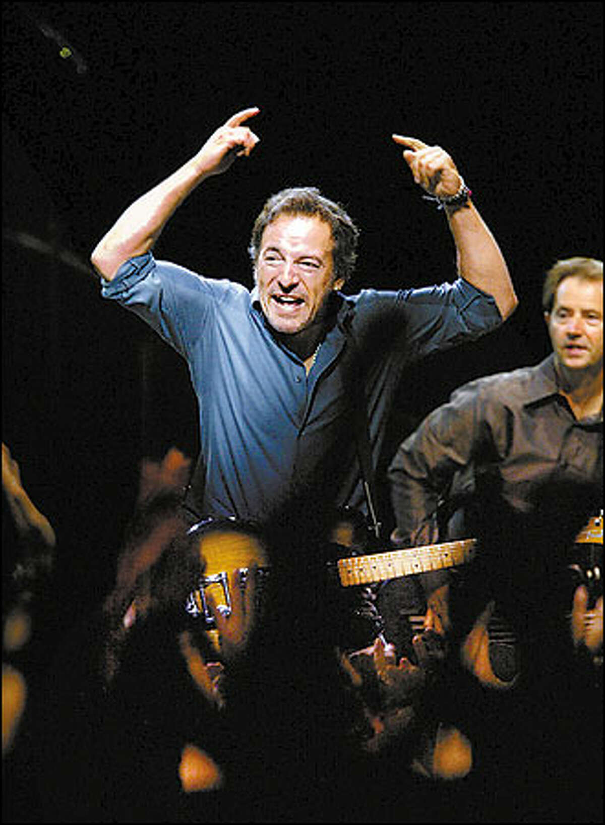 Bruce Springsteen, left, rocks with the E Street Band during the song