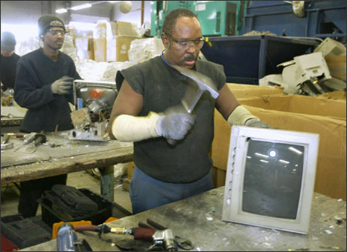 Rickey Trotter of Total Reclaim takes a hammer to an old monitor. The Seattle recycling company charges $10 per computer monitor and 35 cents per pound for other computer gear.
