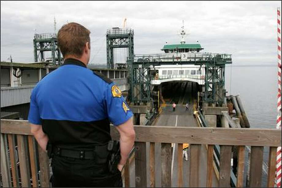 State Trooper Steve Babb stands guard after the ferry Puyallup is evacuated because of a suspicious package found in the men's restroom. Photo: Meryl Schenker, Seattle Post-Intelligencer / Seattle Post-Intelligencer