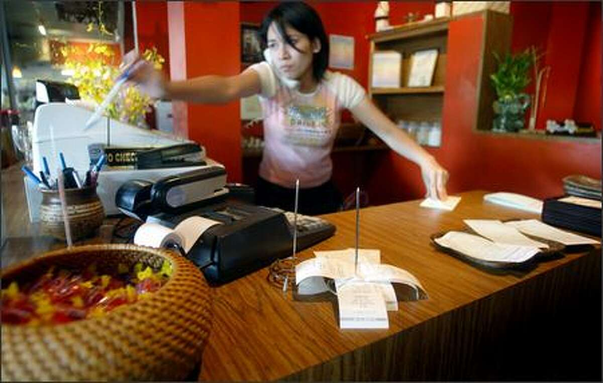 A cashier takes a to-go order Tuesday at Thai 65 in Seattle. The restaurant was unknowingly overcharging customers who paid with credit cards.