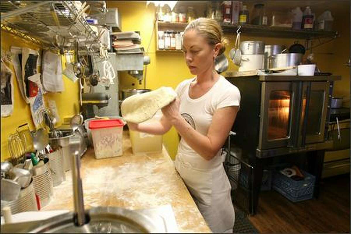 Ericka Burke, chef and co-owner of Volunteer Park Cafe & Marketplace, hand-pulls pizza dough.