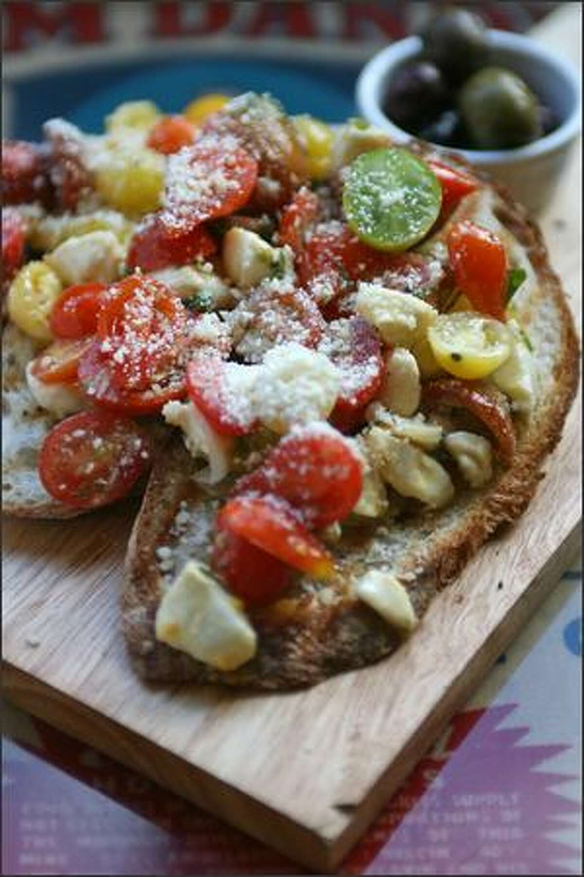 Generous portions of grilled bruschetta are piled with grape tomatoes, sweet onion and creamy dabs of mozzarella.