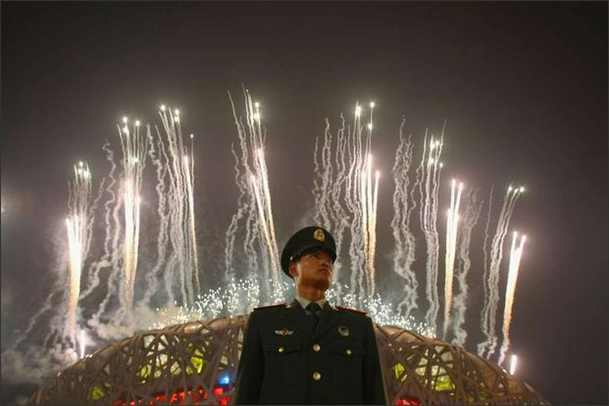 A Chinese policeman stands guard as fireworks explode over the National Stadium during the Closing Ceremony for the Beijing 2008 Olympic Games on Sunday in Beijing.