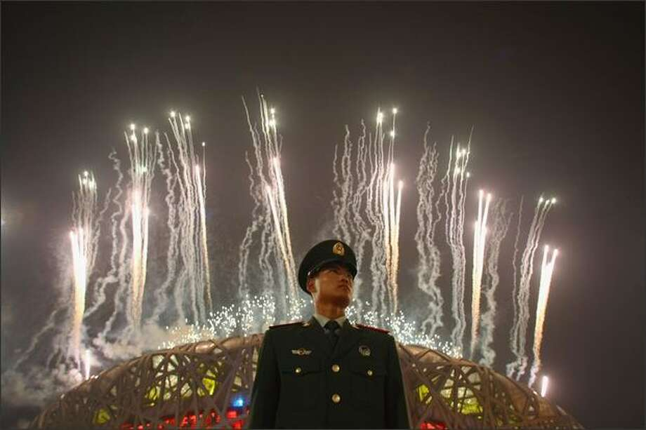 A Chinese policeman stands guard as fireworks explode over the National Stadium during the Closing Ceremony for the Beijing 2008 Olympic Games on Sunday in Beijing. Photo: Getty Images / Getty Images