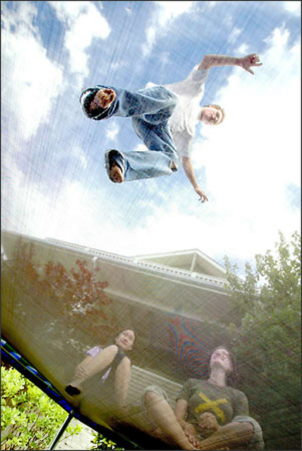 Elliott Swanson, 17, goes airborne as he works on a few trampoline maneuvers in front of his house in Magnolia under - or over - the watchful eyes two friends, Rebecca Gong, at left, and Jessi Knowles.