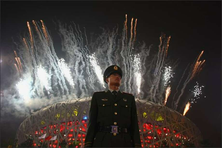 A Chinese policeman stands guard as fireworks explode over the National Stadium during the closing ceremony for the Beijing 2008 Olympic Games on Sunday in Beijing, China. Photo: Getty Images / Getty Images