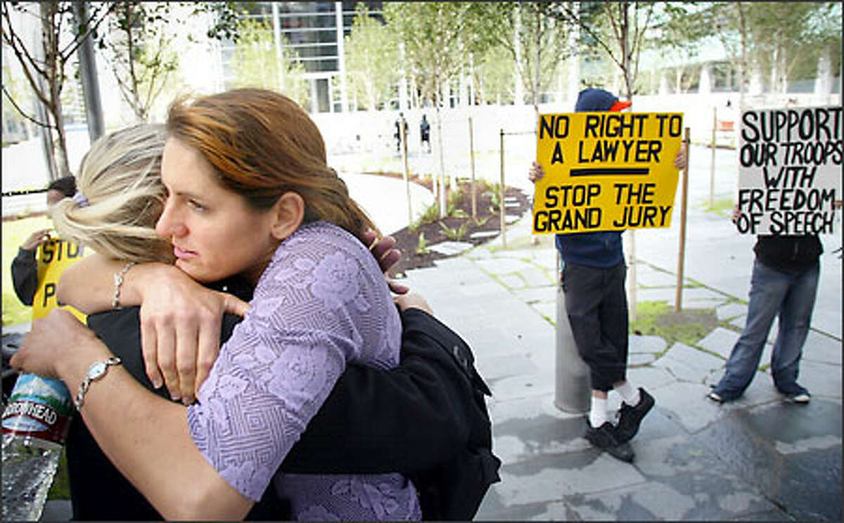 Animal rights activist Gina Lynn, facing camera, gets a hug from friend and fellow activist Allison Lance Watson while standing with supporters outside the U.S. Courthouse in Seattle yesterday. Lynn later refused to testify before a federal grand jury investigating a firebombing at an Olympia timber company.