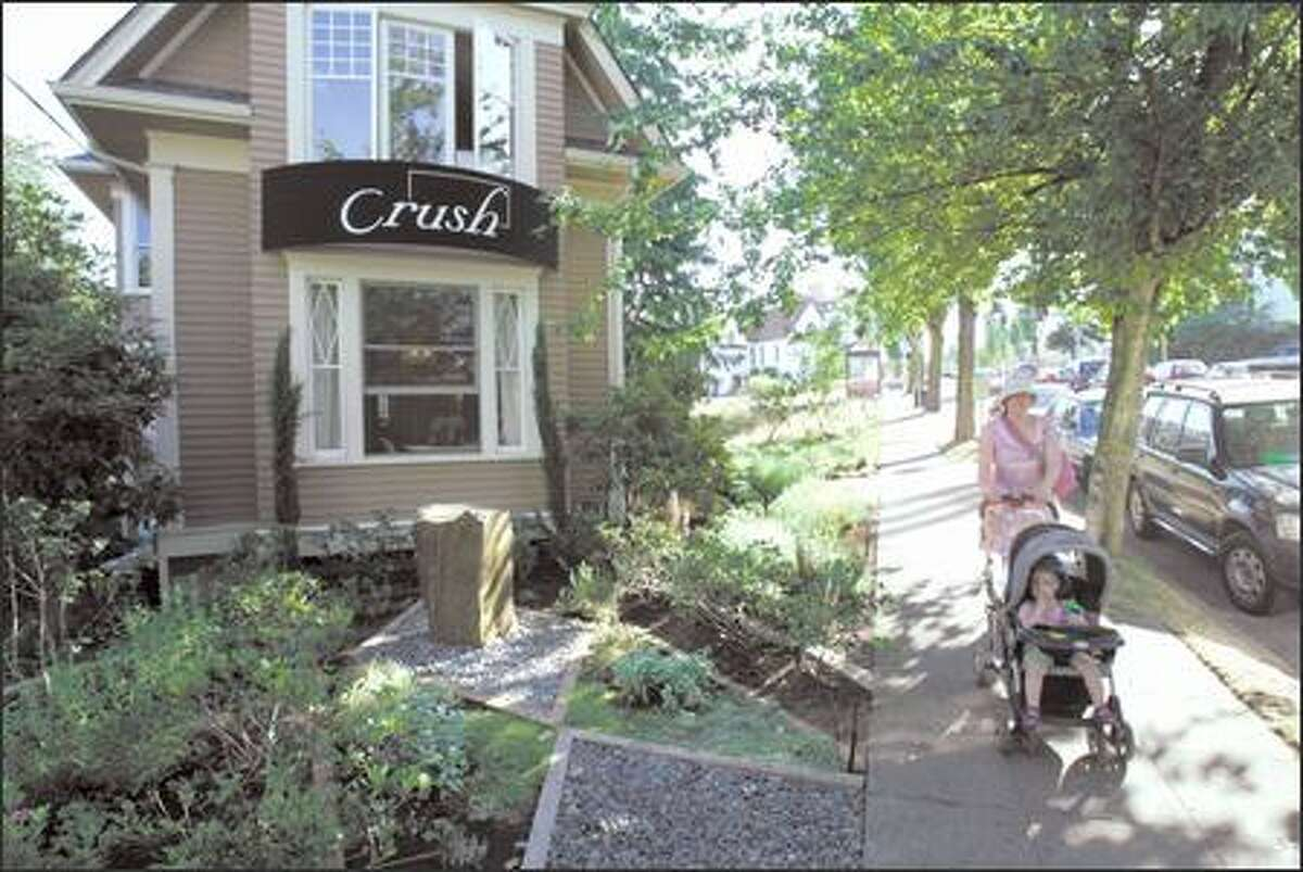 A woman and child stroll past Crush, a new dining enterprise in an owner-remodeled 102-year-old house in the Central Area.