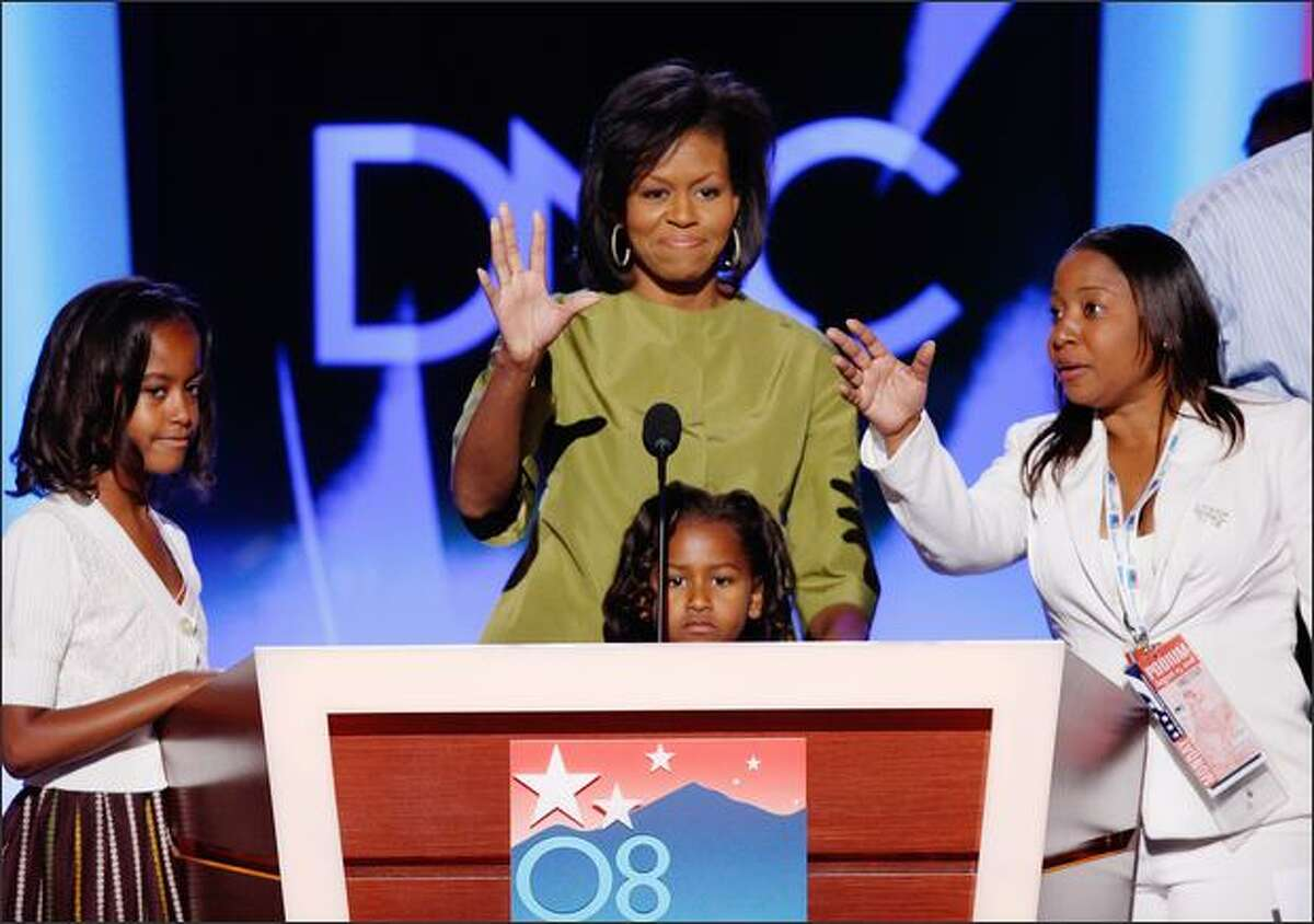 Michelle Obama waves as she looks over the podium with and her daughters Malia, 10, Sasha, 7, at the Democratic National Convention in Denver on Monday. Michelle Obama will address the convention later in the evening.
