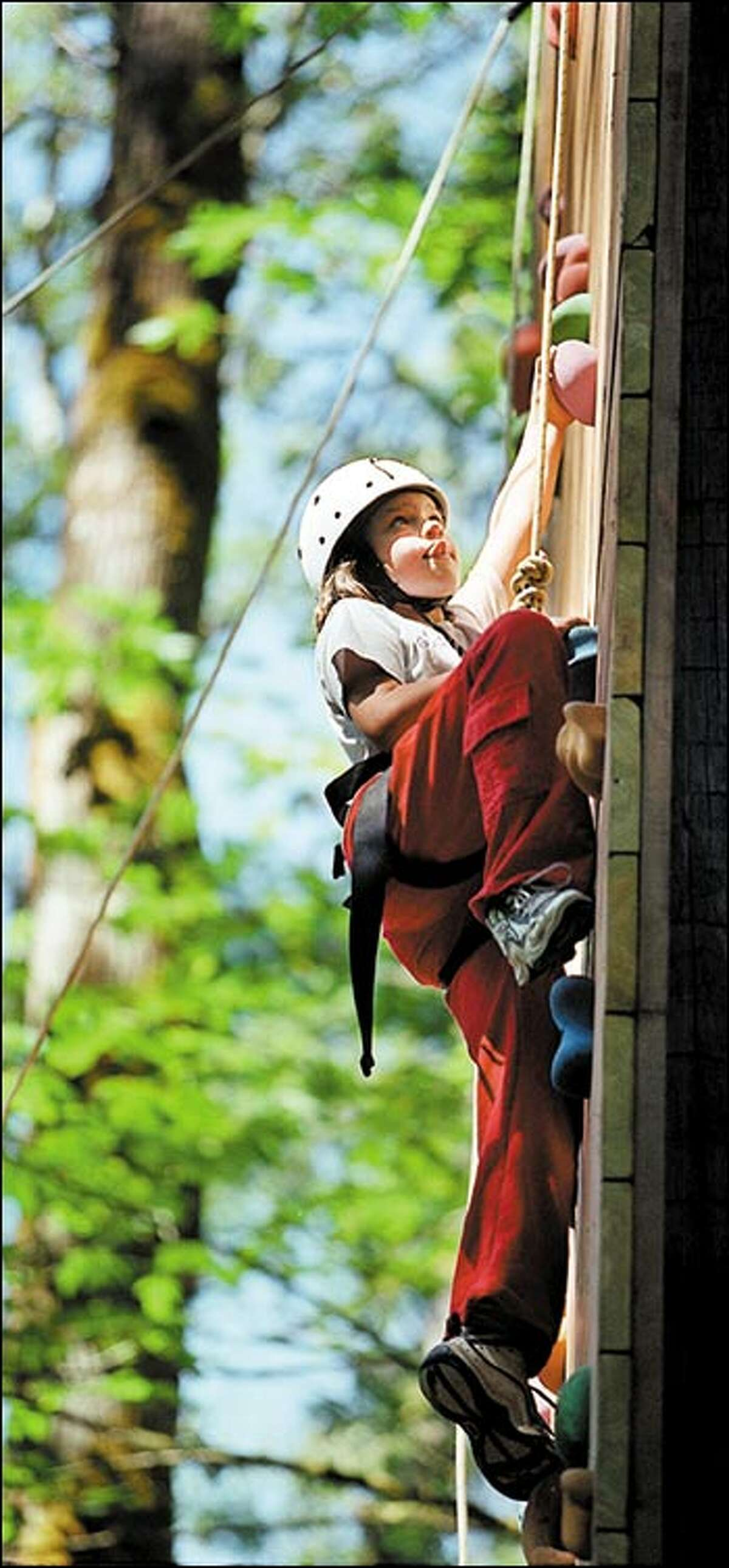 Jen Booth, 10, scales a 40-foot wall at Camp River Ranch in Carnation. The camp is part of a makeover for the Girl Scouts, an 89-year-old institution that has shown a remarkable ability to change with the times.