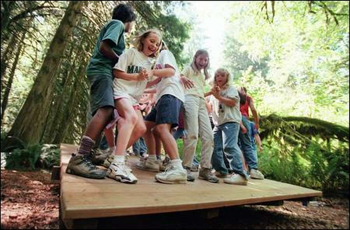 """Scouts struggle to balance on a wooden platform, one of the challenges at Camp River Ranch. """"If it was just about cookies and uniforms, I would drop out,"""" says Jennifer Thompson, 11. """"With Girl Scouts, you can do almost anything you dream."""""""