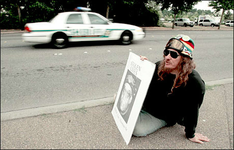 A member of the October 22 Coalition to Stop Police Brutality protests outside the Thomas inquest at the Regional Justice Center in Kent. Photo: Mike Urban, Seattle Post-Intelligencer / Seattle Post-Intelligencer