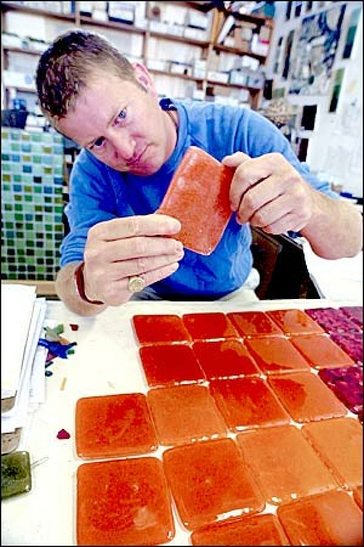J. Penrose, manager of Bedrock Industries' architectural line, checks tiles that will be installed in a remodeled kitchen. The Seattle company, which produces tiles and gifts made of used glass, estimates that it recycles more than 200,000 pounds of glass annually. Bedrock tiles are sold around the country and in its West Garfield Street store.