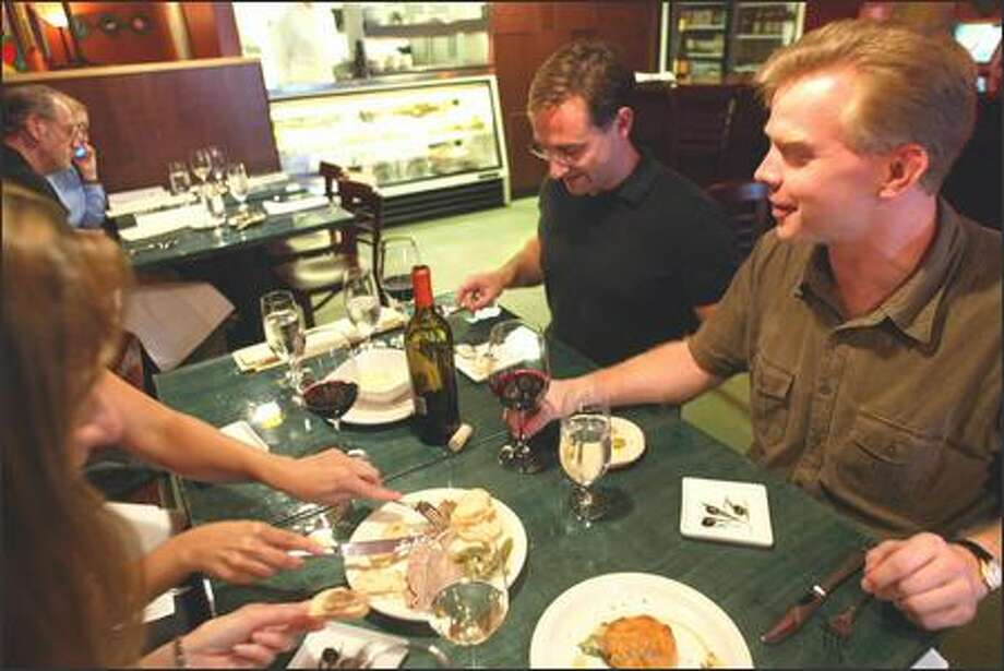 "Paul Hagedorn, left, and Tom Cole enjoy a variety of ""small plate"" items on the menu at Olives Gourmet Foods in Edmonds. ""Big plate"" items for dinner also are available. Photo: Karen Ducey, Seattle Post-Intelligencer / Seattle Post-Intelligencer"