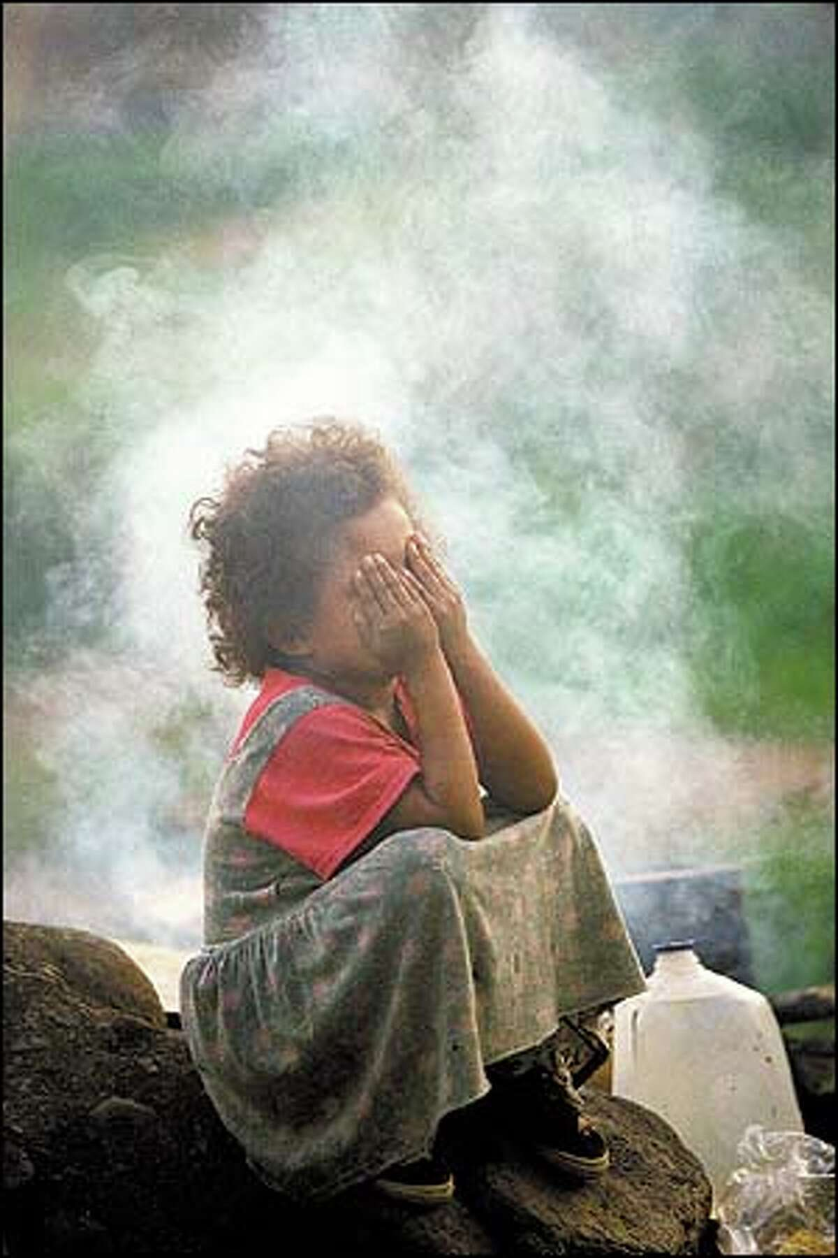 A child covers her eyes from cooking smoke in a makeshift camp for displaced coffee workers and their families in Matagalpa, Nicaragua.