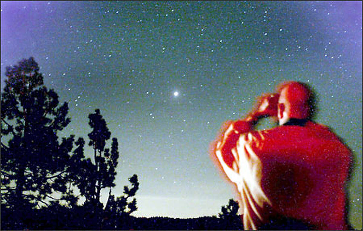 People gather at the Lake Tahoe lookout on the Mt. Rose Highway above Incline Village, Nev., early Wednesday morning, Aug. 27, 2003, to see the planet Mars make its closest approach to Earth in some 60,000 years. Mars is the bright object in the center of the sky.