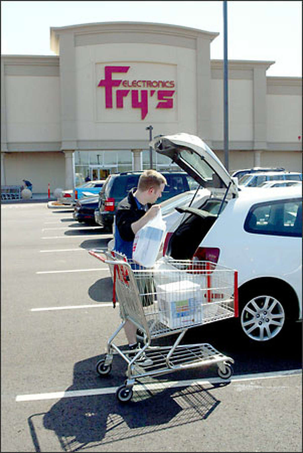 Evan Stoner of West Seattle stocks up at the new Fry's Electronics in Renton. He spent about $300 yesterday at the store, which just opened at 800 Garden Ave. N. It carries computer gear and consumer electronics.