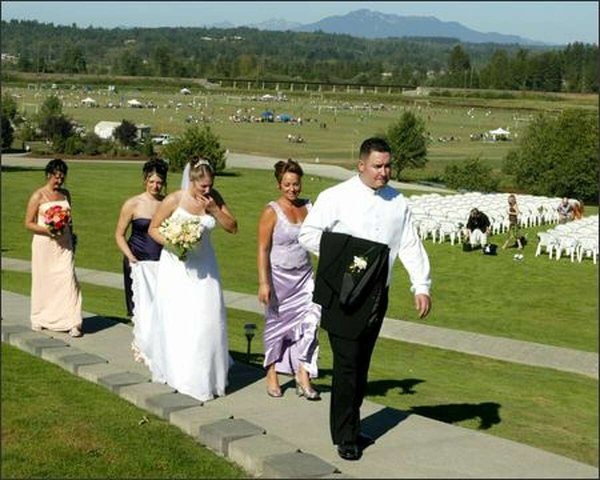 Groom Jim Lambro, followed by his mother, Julie Hunter; bride-to-be, Rachelle Stinde; Katrina Stinde, holding the bridal train; and the bride's mother, Bev Stinde, return from taking wedding pictures at Lord Hill Farms. A soccer tournament is in the background.