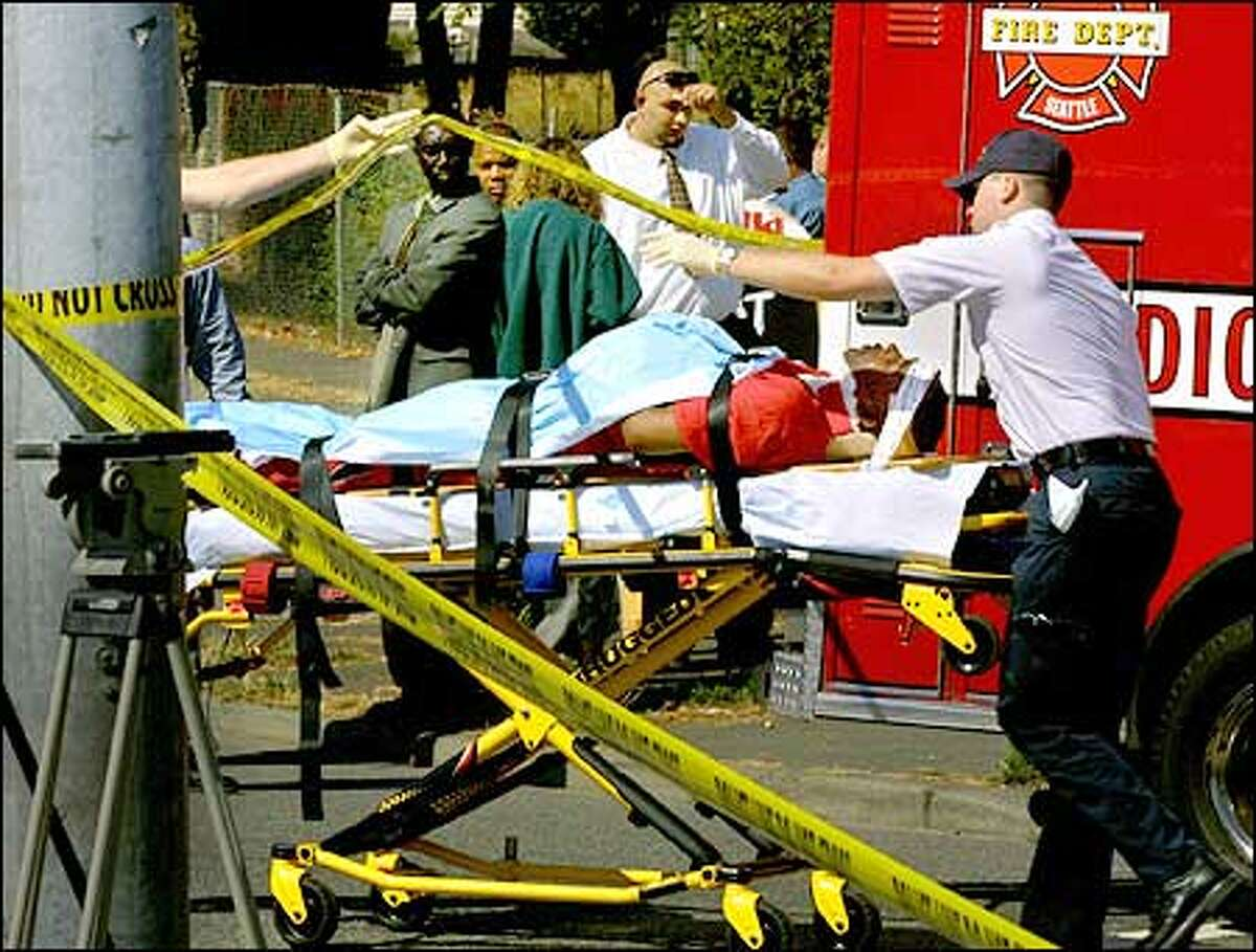 One of those injured when a bus was commandeered is taken away by paramedics at the intersection of Martin Luther King Way Jr. Way and Alaska Street.