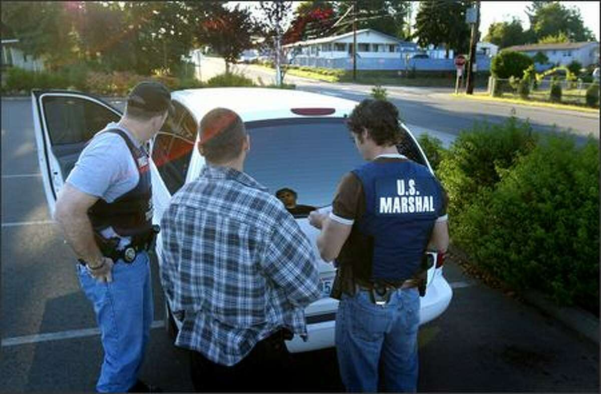 William Steen, with the State Patrol, Ben Hughey, with the Seattle Police Department, and Brian Allan, a deputy with the U.S. Marshals Service, discuss plans to apprehend a fugitive from a home in Renton.
