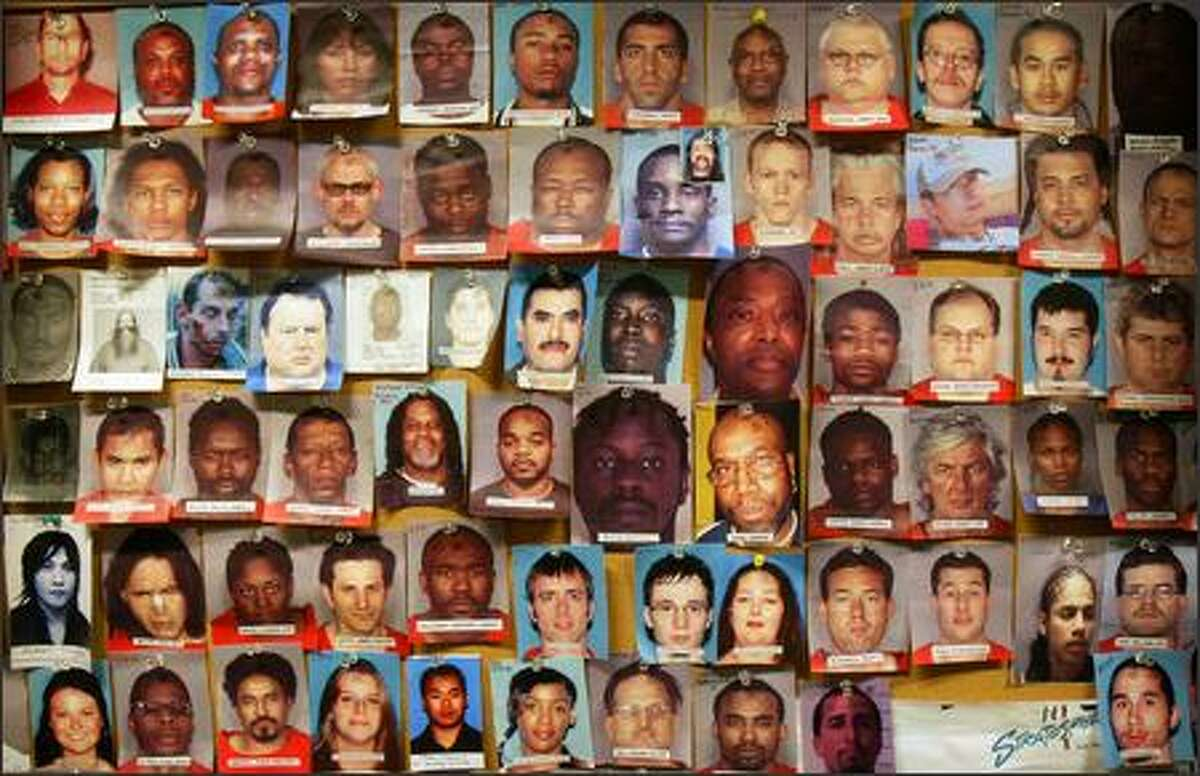 Faces of some of the people captured by the Pacific Northwest Fugitive Apprehension Task Force hang on a wall in U.S. Marshals office in downtown Seattle.