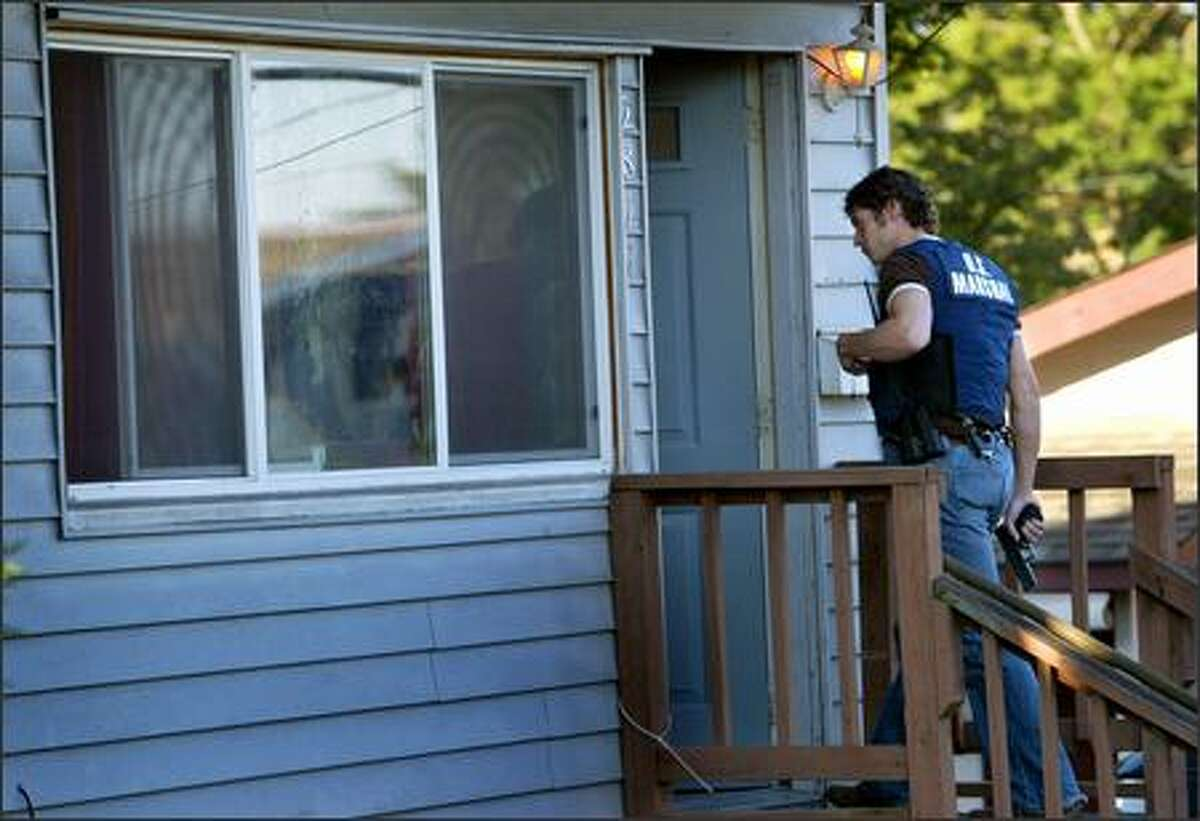 Brian Allan, a deputy with the U.S. Marshals Service, enters a Renton home Friday where officers recently had tracked a fugitive. The man, wanted for child molestation, had left before the early-morning raid and was not caught.