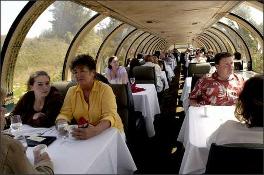 Diners enjoy the sunshine as the train makes it way back to the Tacoma station after its trip to Lake Kapowsin. Photo: Julie Graber, Special To The Seattle Post-Intelligencer / Special to the Seattle Post-Intelligencer
