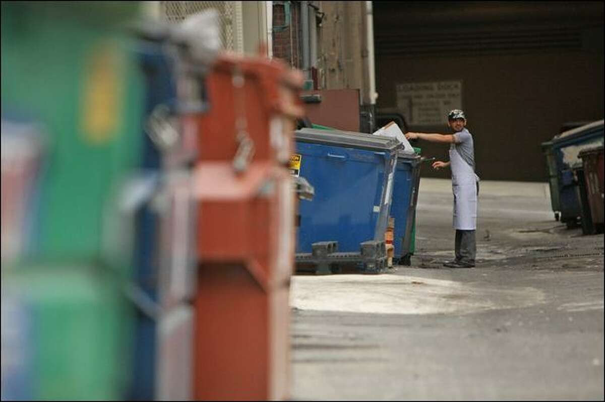 Victor Rios, an employee with Harried & Hungry, a catering company, puts cardboard in a recycling dumpster Wednesday in a downtown Seattle alley.