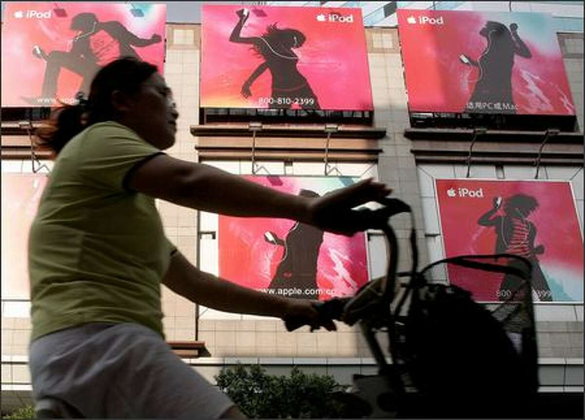 Ads for Apple Computer's iPod greet a bicyclist in Shanghai, China. The popular music players are made outside the U.S., mainly in China.