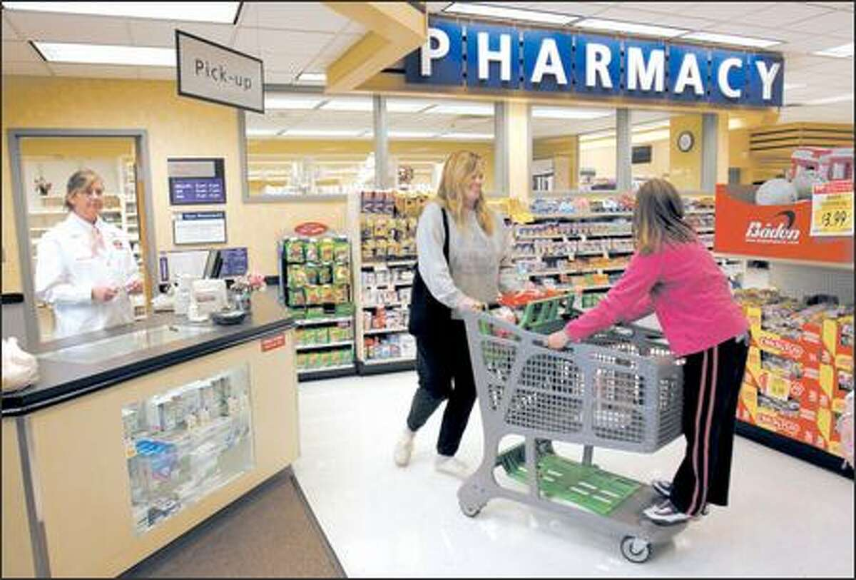 Molly Wren of Shoreline wheels her daughter, Jennifer, 8, away from the TOP Food and Drug pharmacy after getting a prescription from pharmacist Cindy Widmaier.